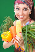 Pretty girl with vegetables on the green background — Stock Photo