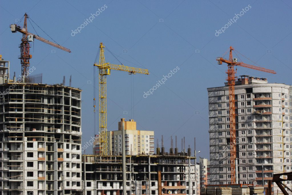 Construction cranes and buildings on blue sky background — Stock Photo #9604960