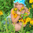 Beautiful young girl surrounded by flowers. — Stock Photo