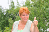 """Middle-aged woman shows a gesture of """"excellent."""" — Stock Photo"""