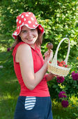 Beautiful girl with a basket of strawberries and white fungus. — Stock Photo