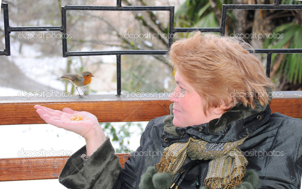 A woman feeds a bird — Stock Photo #10673254