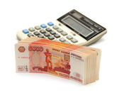 A stack of five thousandth of notes next to the calculator — Stock Photo