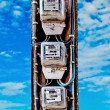 The Old electric meter on blue sky background - Stock Photo