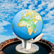 The Sculpture of world in hand on blue sky background — Stock Photo