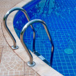 The Closeup of swimming pool with staircase at hotel - Stock Photo
