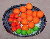 The Sculpture of orange and tomato and lemon on bamboo basket — Stock Photo
