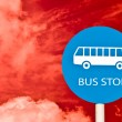 Stock Photo: The Sign ofBus Stop on post pole isolated on red sky background