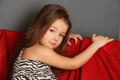Little girl on a red sofa — Stock Photo