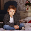 Beautiful boy in an interior in a bedroom — Stock Photo