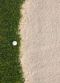 Golf ball and sand bunker — Stock Photo