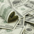 Heart shaped 100 dollar bill on pile of money — Stock Photo #9309994