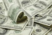 Heart shaped 100 dollar bill on pile of money — Foto Stock