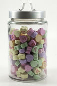Jar with lid filled with valentine hearts — Stock Photo