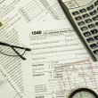 Stockfoto: 1040 tax form, calculator, glasses, compass and money
