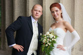 Bride and groom are stay at the column — Stock Photo