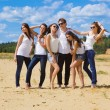 Group of six friends all in blue jeans and white — Stock Photo