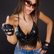 Attractive brunette in denim skirt showing middle finger studio — Stock Photo #9229032