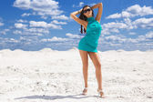 Cute young sexy woman in green dress on the snow — Stock Photo