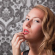 Beautiful blond woman with finger on her lips — Stock Photo