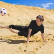 Stock Photo: Young man playing soccer on beach