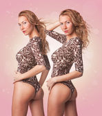 Two cute sexy blond twins girls in swimsuit on pink background — Stock Photo
