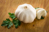 Fresh garlic head and cloves on wood — Stock Photo
