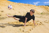 Young man playing soccer on beach — Stock Photo