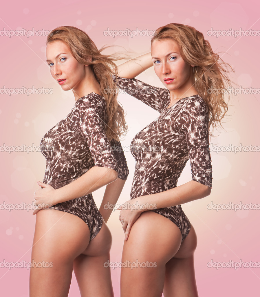Two cute sexy blond twins girls in swimsuit on pink background — Stock Photo #9248576