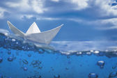 Paper ship splash with bubbles sailing in blue water and sky — Stock Photo