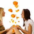 two cute twins girls having fun under orange rain on a white bac — Stock Photo