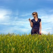 Cute young blond girl on a field in summer, blue sky — Stock Photo