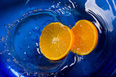 Oranges in water blue background — Stock Photo