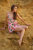 Cute young brunette girl in dress with roses by the sand — Stok fotoğraf