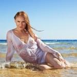 Sexy blonde woman wearing white wet shirt on beach — Stock Photo
