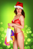 Very sexy Mrs. Santa Claus girl in red underwear, holding gifts — Stock Photo