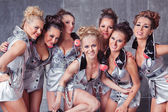 Group of seven happy smiling cute girls in silver go-go costume — Stock Photo