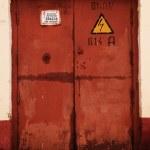 Grunge rusty orange door, danger high voltage keep out in russia — Stock Photo