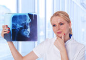 Portrait of attractive woman doctor looking at X-ray results of — Stock Photo
