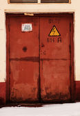 Grunge rusty orange door, danger high voltage keep out in russia — Stock Photo