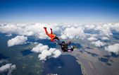 Two skydivers flying over the clouds — Stockfoto