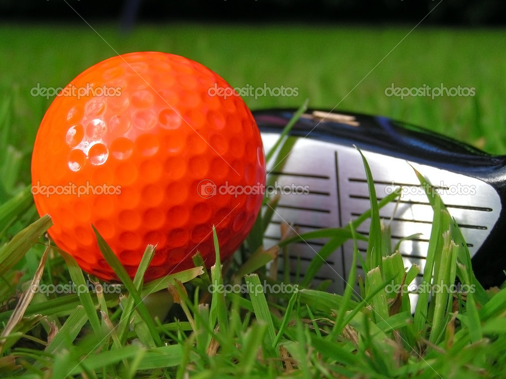 An orange golf ball on tee with club  Stock Photo #9253452