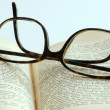Open book and eyeglasses — Stock Photo