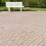 White garden bench on paved walk — Stock Photo #10321989