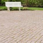 White garden bench on paved walk — Stock Photo