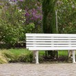 White garden bench on red paved walk — Stock Photo