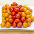 Red yellow and orange cherry tomatoes on white plate — Stock Photo