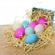 Small basket with colorful eggs spilling out - Foto de Stock