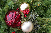 Christmas arrangement with greens and ornaments — Stock Photo