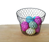 Wire basket of colored eggs — Stock Photo
